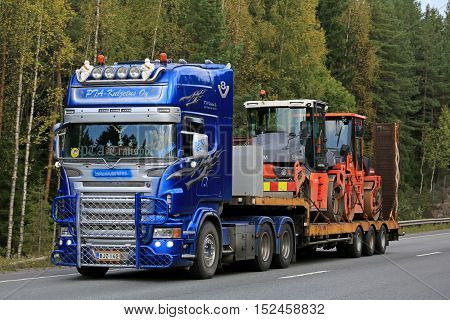 ORIVESI FINLAND - SEPTEMBER 1 2016: Customized Scania V8 of PTA-Kuljetus transports roadworks equipment along autumnal road in Finland.