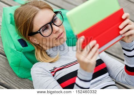 Girl with Tablet PC in hands lying on wooden surface