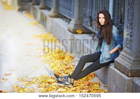 Beautiful long-haired girl in a denim jacket and boots sitting beside a beautiful wrought iron fence in downtown autumn day.