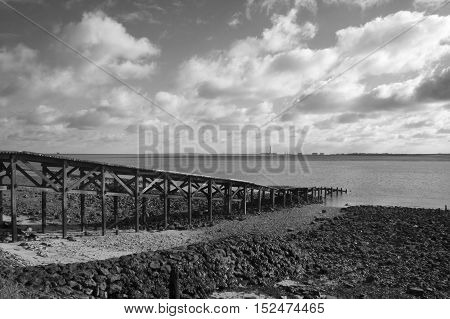 Black and white image of an old wooden jetty on Canvey Island Essex England