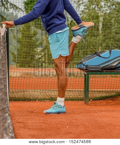 photo of male tennis player stretching before playing