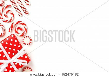 Christmas Side Border Of Red And White Gifts And Peppermint Candies Over A White Background