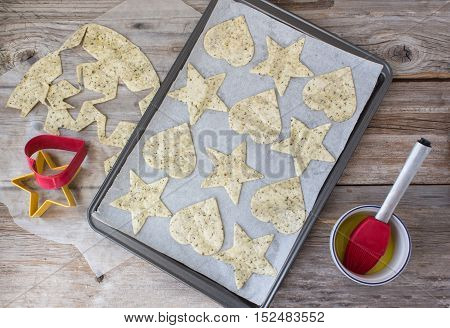 horizontal image of the process of the makings of tortilla chips made into heart and star shapes lying in cookie sheet with some left over tortilla dough and a cookie cutter on rustic wood surface.