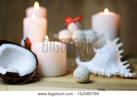 little sweet candies in coconut flakes and surrounded by burning candles and fresh coconut