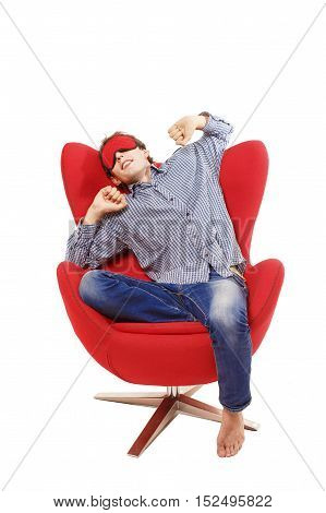 sleepy man stretching on a chair. guy wearing a mask for sleep dozing in armchair. the concept of couch potato. isolated on white background