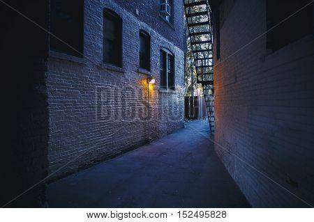 burning lantern in a dark alleyway. city backyards