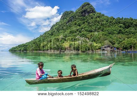 Semporna,Sabah-Sept 10,2016:Sea Gypsy kids on a boat on 10th Sept 2016 at Semporna,Sabah.This sea gypsies kids are given a net & taught to catch fish,octopus & lobsters off their unique handmade boats