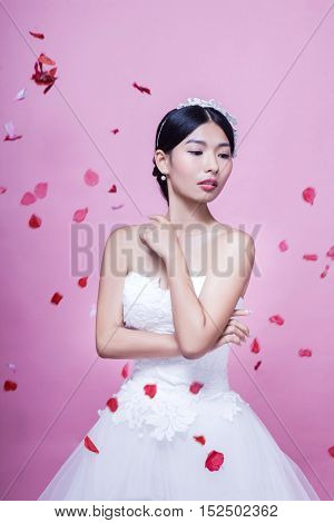 Beautiful bride with rose petals in mid-air standing against pink background