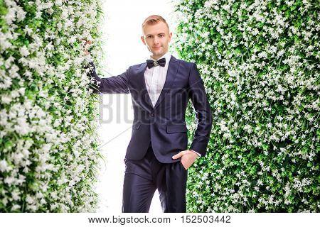 Portrait of confident bridegroom standing amidst flower decorations