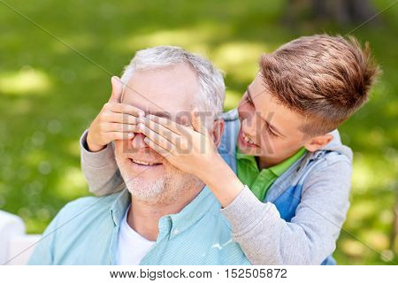 family, generation and people concept - happy grandfather and grandson playing guess who game at summer park