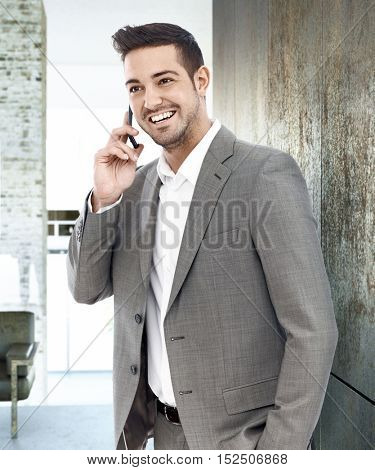 Happy young businessman standing by wall, talking on mobilephone, looking away.