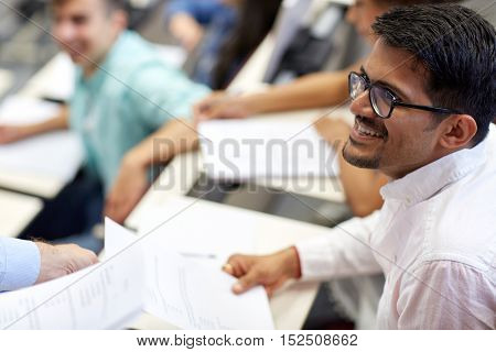 education, high school, university, learning and people concept - teacher giving exam test to smiling indian student man at lecture