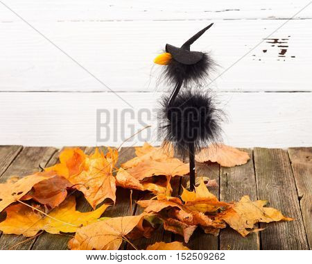Toy crow in a cap and autumn leaves. On an old table there is a toy in a hat of the witch. The yellow whithered autumn leaves are scattered