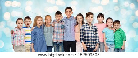 childhood, fashion, friendship and people concept - group of happy smiling children hugging over blue holidays lights background