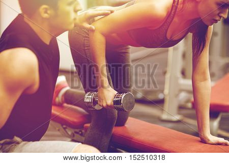 fitness, sport, exercising and weightlifting concept - close up of young woman and personal trainer with dumbbells flexing muscles in gym