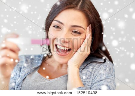 pregnancy, fertility, maternity, emotions and people concept - happy smiling woman looking at pregnancy test at home over snow