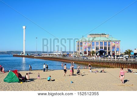 WEYMOUTH, UNITED KINGDOM - JULY 18, 2016 - Holidaymakers on the beach with the Pavilion and Jurassic Skyline tower to the rear Weymouth Dorset England UK Western Europe, July 18, 2016.