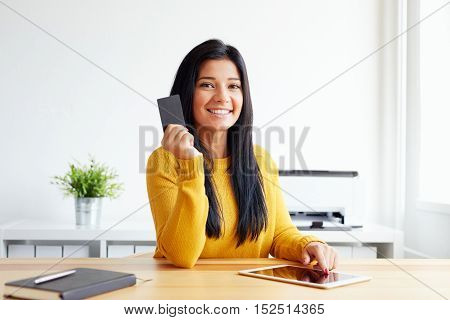 Happy Woman In The Office With A Credit Card And Tablet Computer