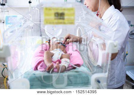 The doctor examined her newborn baby in a hospital room after the birth.