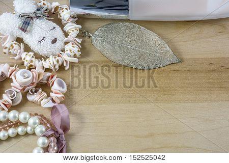 Girl's pink bijouterie, bracelets on light wooden background