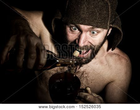 Dark portrait of scary evil sinister bearded man with smirk, he pours brandy in a cup of coffee. strange Russian man with a naked torso and a woolen hat.