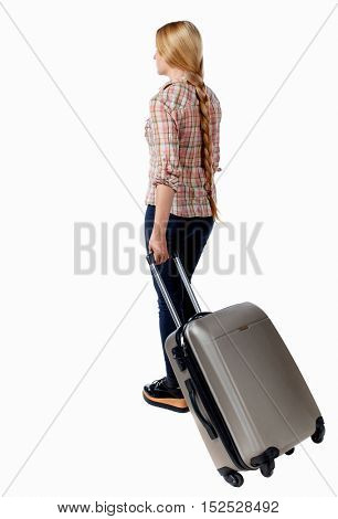 Back view of woman with suitcase looking up. Standing young girl. Rear view people collection.  backside view of person. Isolated over white background. Girl with very long hair rolls suitcase