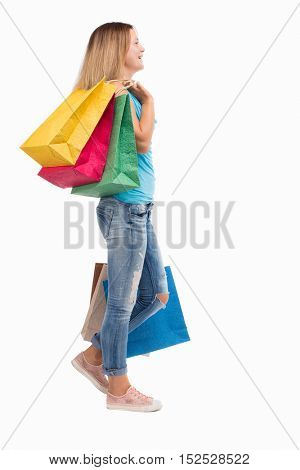 back view of going  woman  with shopping bags . beautiful girl in motion.  backside view of person.  Isolated over white background. blonde in a blue sweater misses with colored blocks on the shoulder