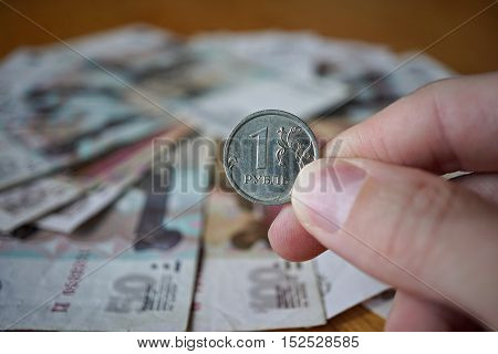 Male hand holding a Russian coin (Russian Ruble, RUB) with a background created of Russian bank notes in the shape of circle