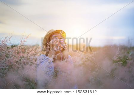 Woman blowing bubbles in meadow. travel and sunset soft and select focus