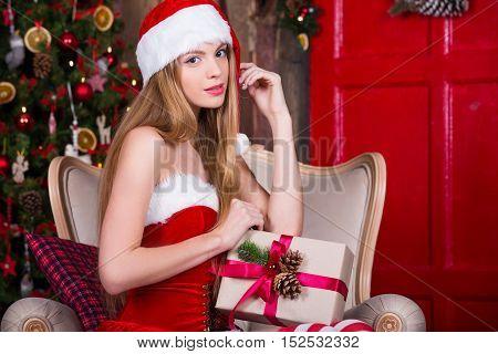 Cute Santa girl dreaming near the Christmas tree, making a wish. Vintage new year atmosphere. Xmas dreams.