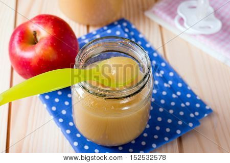 Closeup homemade baby apple sauce on a wooden background