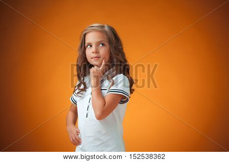 The Cute Thoughtful Little Girl On Orange Background