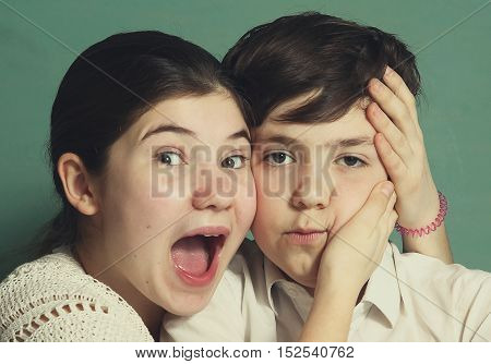 teen siblings brother and sister grimacing close up portrait. Boy girl siblings grimace.