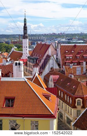 Red roofs and the tower of the Church of the Holy Spirit (from 14th century) in Tallinn Old Town .
