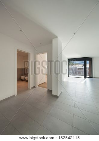 Interior of empty apartment, wide living with tiled floor