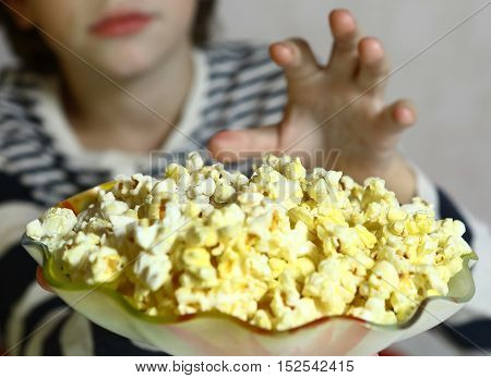 kids hand crab pop corn close up photo. Kid eat popcorn.