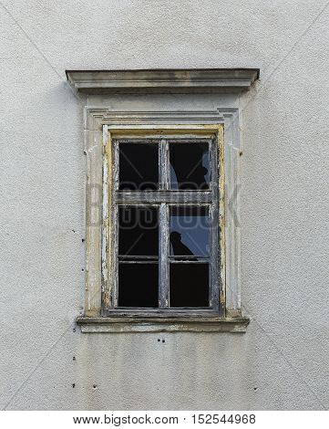 Vandalized window on a building with bullet marks.