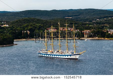 Modern ship with masts and sails similar to the old frigate. Located in the sea on a background of the island.