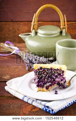 Bilberry, blueberry tart with lavender on white plate, wooden background, vintage style