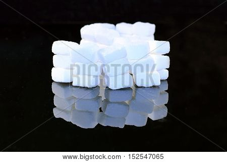 Lump sugar cube isolated on black mirroring background.