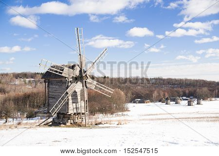 Windmill against a blue sky with clouds