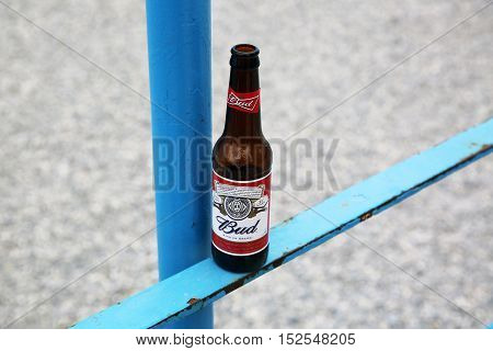 Menton France - May 14 2016: Bottle of Budweiser Beer on a Blue Metal Fence Beach in the Background