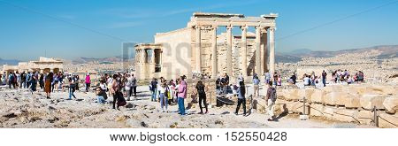 Athens, Greece - October 14, 2016: Panoramic view with tourists taking photo near Erechtheum temple ruins decorated with Caryatids female statues in Acropolis