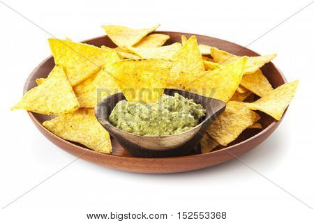Nachos. Wooden plate with tortilla chips and Guacamole in bowl isolated on white background