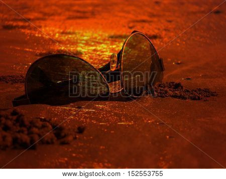Sunglasses reflecting beautiful sunset colors on a beach during the holidays.