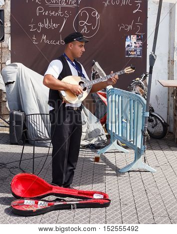 Young Street Musician Playing The Lute On The Waterfront