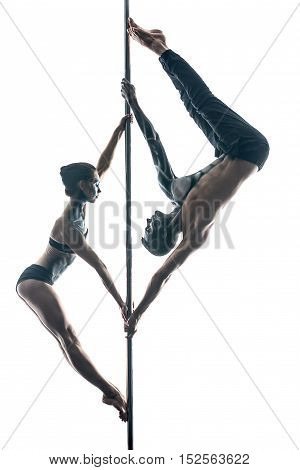 Incredible couple of pole dancers with horrific body-art are hanging face to face on a pylon in the studio on a white background. Guy hangs upside down. They dressed in black sportswear. Vertical.