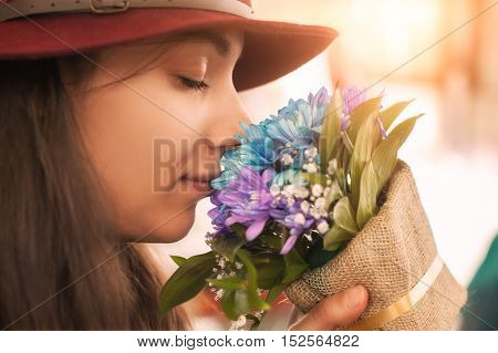 Young woman smelling flowers bouquet in a flowers shop