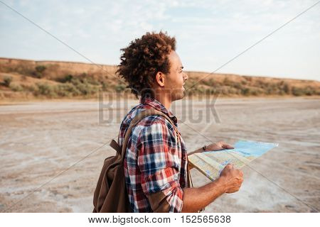 Handsome african american young man with backpack stading outdoors and using map