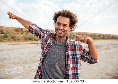Potrait of smiling african young man with backpack pointing away by both hands outdoors